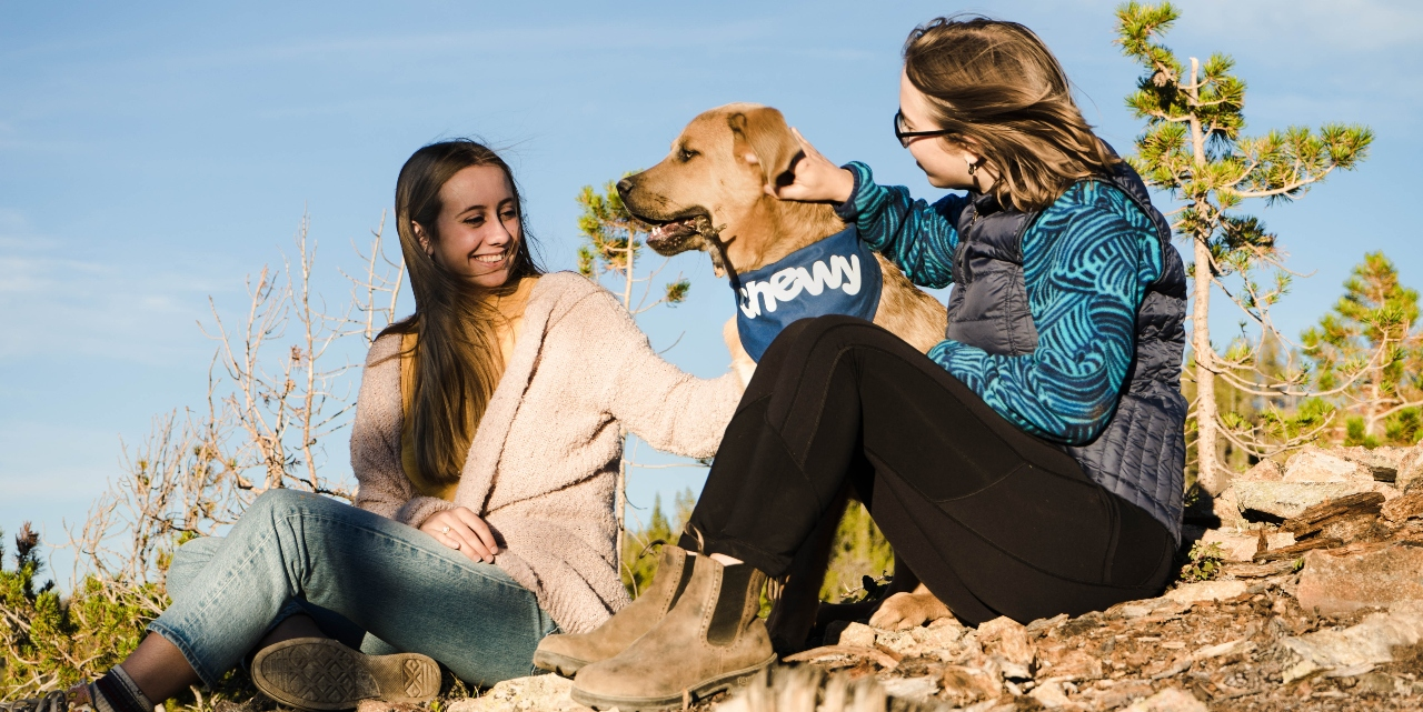 girls sitting with a dog